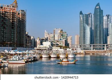 Busan, South Korea - April 2019: Minlaghang Fisherman Wharf backgrounded by skyscrapers of Marine City in Haeundae District and Gwangandaegyo Bridge (Diamond Bridge) in Busan, South Korea