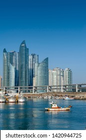 Busan, South Korea - April 2019: Minlaghang Fisherman Wharf backgrounded by skyscrapers of Marine City in Haeundae District and Gwangandaegyo Bridge (Diamond Bridge) in Busan, South Korea