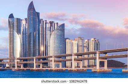 Busan, South Korea. Cityscape of Haeundae District with luxury skyscrapers and bridge in evening light