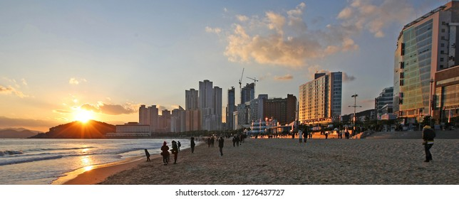 Busan, South Korea - December 10, 2011: A sunset at Haeundae Beach in Busan, South Korea. The beach is a popular spot for visitors and locals thanks to its beautiful views and cafes and restaurants.