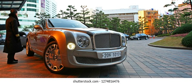 Busan, South Korea - December 3, 2011: A valet waits by a Bentley luxury sedan car. Taken in front of a casino in Busan, South Korea, but suitable to illustrate wealth, luxury, and wealthy lifestyle.