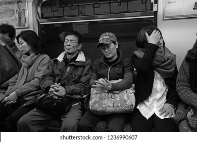 Busan, South Korea - March 11, 2012: Commuters on a busy and crowded subway in Busan, South Korea. Despite the country's affluence, many of its people are often stressed and work long hours.