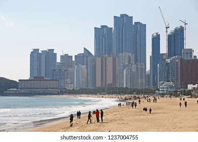 Busan, South Korea - March 24, 2012: People enjoying a beautiful sunny day at Haeundae Beach in Busan. The long, sandy beach in the middle of the busy city is popular with locals and tourists alike.