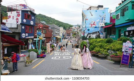 Busan, South Korea - May 29, 2018: Some of the tourists walk along a street of Gamcheon Culture Village with traditional Korean Culture attires and take pictures. It attracts many foreigners for tour.
