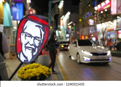 Busan, South Korea - October 13, 2012: The famous face of Colonel Sanders is reflected in a mirror on the streets of Busan. American-based fast food restaurants are increasingly popular all over Asia.