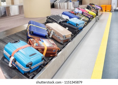 Busan, South Korea - October 6, 2017: Bright suitcases and bags on luggage conveyor belt at arrival area of passenger terminal in Gimhae International Airport. Baggage carousel.