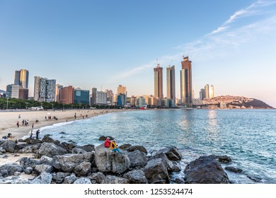 Busan, South Korea - Sep 10th 2018 - Tourists and locals having fun in the rocks of Haeundae with buildings close to the sand in the late sunset of Busan