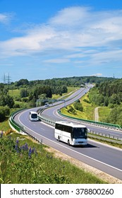 Buses on the highway with electronic toll gates in a countryside. The view from above. Sunny summer day with blue skies and white clouds.
