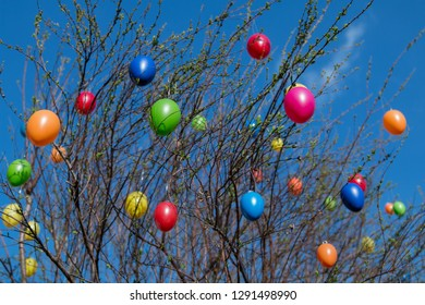 bush with colorful plastic easter eggs and blue sky