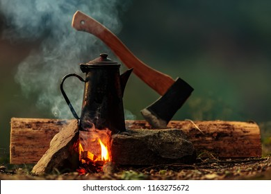 bush craft still life, pot of water to tea aboce fire with axe background