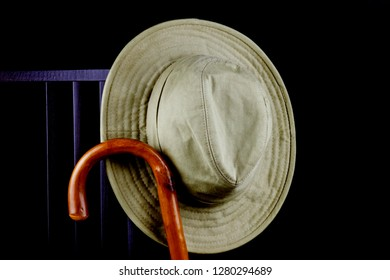 Bush hat and walking stick hanging on a chair isolated on black