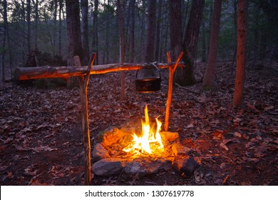Bushcraft campfire for cooking with primitive debris hut shelter in the background. Wilderness survival skill