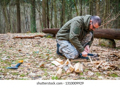 bushcrafting man with knife cutting a wooden stick for campfire in the forest