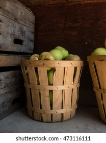 A bushel of apples for sale next to vintage wooden produce crates at a farm stand.