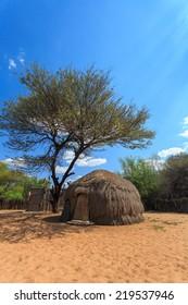 Bushman San people traditional huts in Kalahari Botswana.