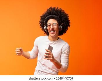 Bushy millennial black guy singing into smartphone like microphone and listening to music via wireless earphones, orange background