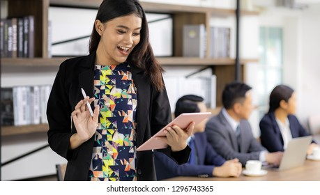 Busineeswoman standing and using tablet with her team meeting in background