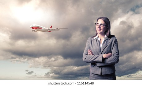 Busines person and plane on the background against cloudy sky
