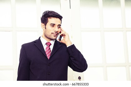 Businesman is making decision on phone outside the office.
