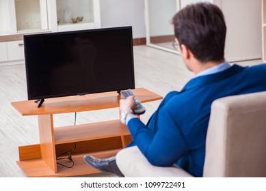 Businesman watching tv in office