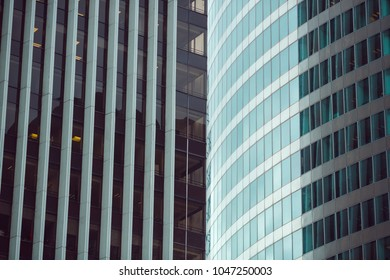 Business abstract - modern office building covered with glass against blue sky. Details of architecture