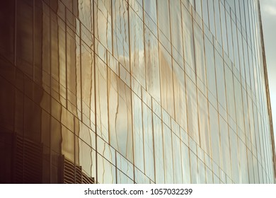 Business abstract - modern office building covered with glass against blue sky. Copy space. Details of architecture