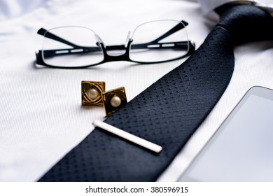 Business accessories (cufflinks, fountain pen, tablet, phone, glasses, notepad) in the men's classic white shirt with tie. Macro with blur and soft focus.