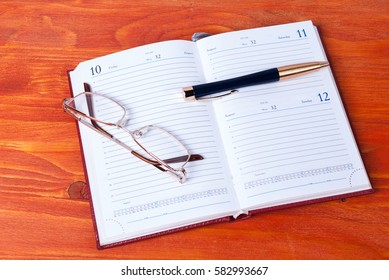 Business accessories - diary, glasses and pen on the wooden table