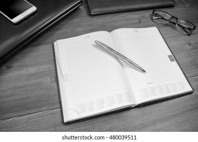 Business accessories (diary, notebook, mobile phone, fountain pen, glasses) on a wooden office desk. Soft focus. Top view.