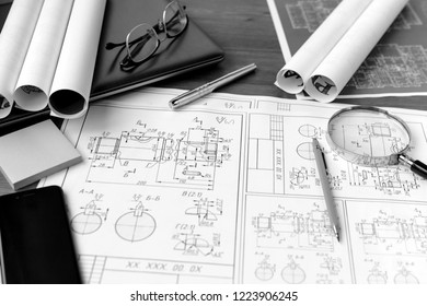 Business accessories (laptop, smartphone, pens, magnifier), accessories for drawing (plans, rulers) and learning on the table
