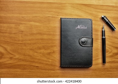 Business accessories on desktop: notebook, diary, fountain pen. Macro with blur and soft focus