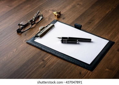 Business accessories on desktop: notebook, diary, fountain pen, cufflinks, glasses. Macro with blur and soft focus. With vignette