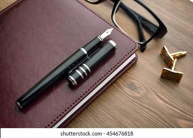 Business accessories on desktop: notebook, diary, fountain pen, cufflinks, glasses.