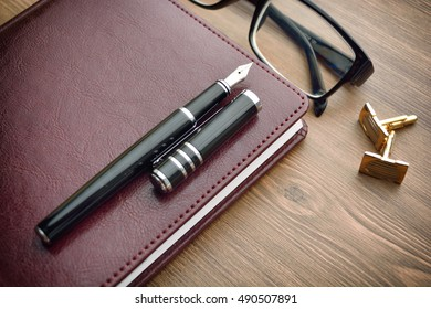 Business accessories on desktop: notebook, diary, fountain pen, cufflinks. Soft focus.