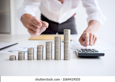Business accountant or banker, businessman calculate and analysis with stock financial indices and putting growth stacking coin and financial costs wisely and carefully, investment and saving concept.