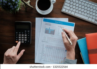Business accounting concept, Business man using pen pointing  with data budget planner chart and calculator for calculate finanance plan  paper in office.