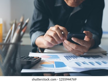 Business accounting. Man accountant using mobile phone. Businessman working, reviewing business marketing financial report with cup of coffee, calculator on desk in modern office, toned, close up
