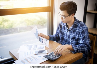Business accounting people, saving, finance and economy concept. Serious Asian businessman using calculator for calculations documents , charts and graphs. Asia male model in his 30s