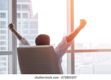 Business achievement concept with happy  businessman relaxing at work in office room, resting and raising fists with ambition success looking forward to city building urban scene through glass window