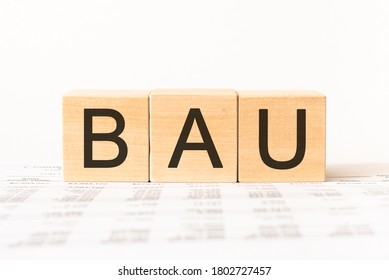 Business Acronym BAU - Business As Usual. Wooden small cubes with letters isolated on white background with copy space available. Business Concept image.