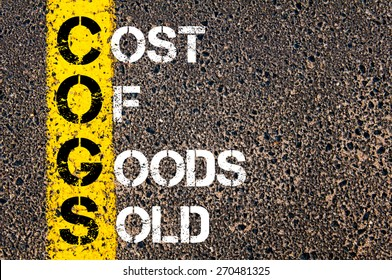 Business Acronym COGS - Cost of Goods Sold. Yellow paint line on the road against asphalt background. Conceptual image