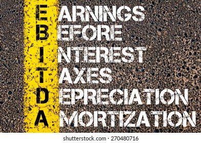 Business Acronym EBITDA - Earnings before Interest, Taxes, Depreciation, and Amortization. Yellow paint line on the road against asphalt background. Conceptual image