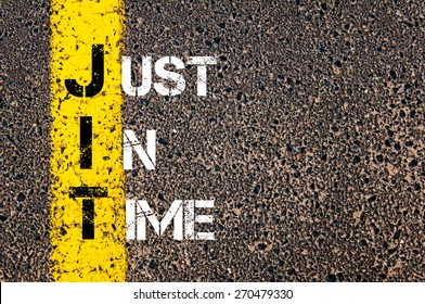 Business Acronym JIT - Just In Time. Yellow paint line on the road against asphalt background. Conceptual image