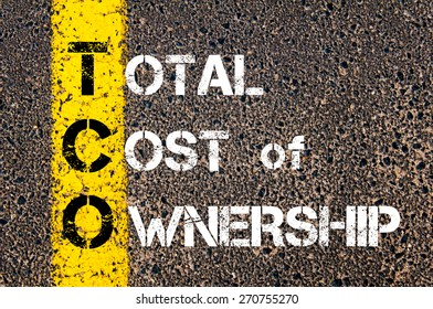 Business Acronym TCO as Total Cost of Ownership. Yellow paint line on the road against asphalt background. Conceptual image