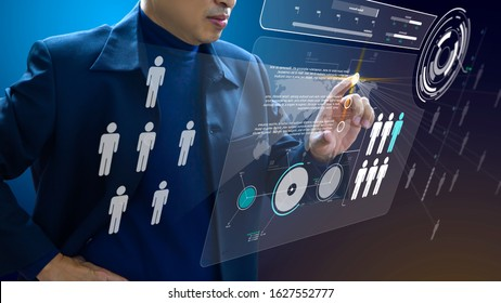 Business administrator in action of manpower or human resource planning or business organisation on a futuristic augmented reality virtual dashboard.