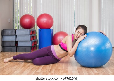 Business, Advertisement, Fashion concept - Asian woman relaxing after exercise session. Tired female athlete lying on the floor at gym.