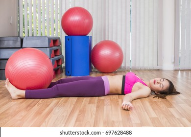 Business, Advertisement, Fashion concept - Asian woman lying on floor and looks very tired and catching her breath after working out in gym.