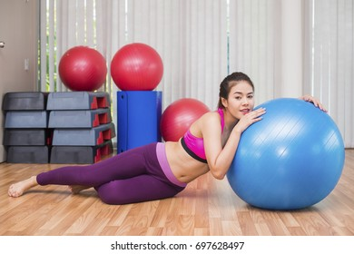 Business, Advertisement, Fashion concept - Asian woman at gym with yoga ball shot. Tired exhausted but still smile
