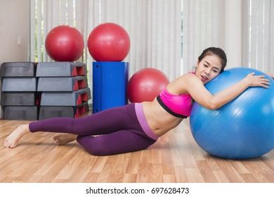 Business, Advertisement, Fashion concept - Tired asian woman trying to lose weight and doing stretching fitness exercise on fitness ball in gym.