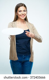 Business advertising concept with young smiling woman holding empty plate and finger pointing.